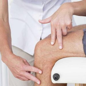 A doctor checking his patient knee for 'venaseal vein treatment'