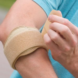 A man is detenting bandage who is suffering from 'Elbow Bursitis'