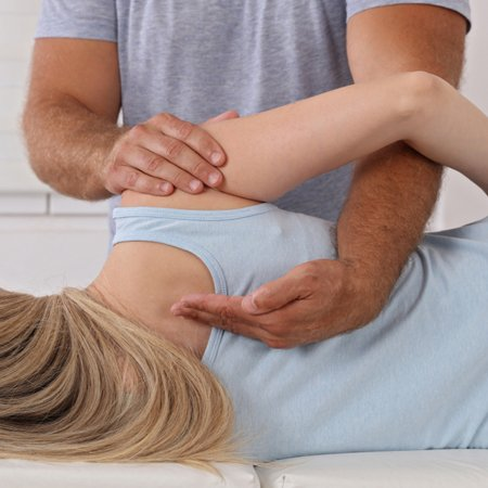 A physician examining the spine of a young lady at Complete Medical Wellness New Jersey
