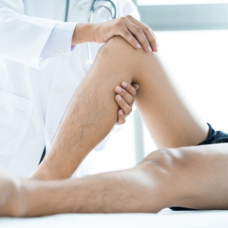 Orthopedic specialist checking up the knee of a guy at Complete Medical Wellness New Jersey