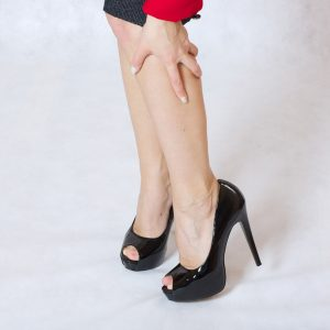 A woman is suffering from severe 'leg pain', holding her leg