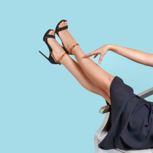 A young lady relaxing on a chair & looking at her legs after taking 'ClariVein treatment' from Complete Medical Wellness New Jersey