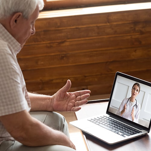 An old man is having online appointment with her doctor
