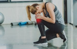 A female athletic at gym holding her knee due to chronic knee pain