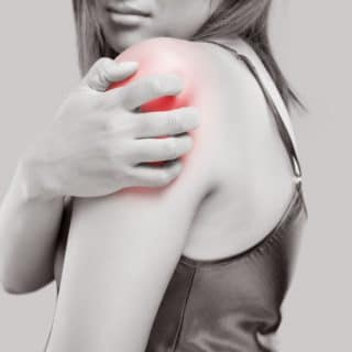 A woman holding her shoulder and feeling severe shoulder pain